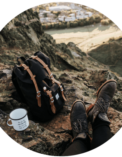 backpack and mug on a cliff
